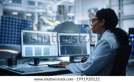 Female Engineer uses Computer to Analyse Satellite, Calculate Orbital Trajectory Tracking. Aerospace Agency International Space Mission: Scientists Working on Spacecraft Construction. Over Shoulder Foto stock ©