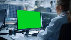 Female Engineer uses Green Screen Computer to Analyse Satellite. Aerospace Agency Manufacturing Facility: Scientists Develop, Assemble Spacecraft for Space Exploration Mission. Over Shoulder