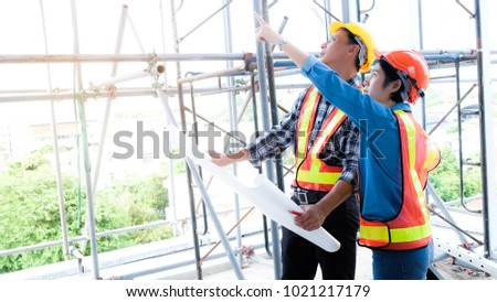Female engineers and male engineer work meeting and pointed to the painting in the site project to consult.Engineering and Construction Engineering Tools #1021217179