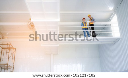 Female engineers and male engineer work meeting and pointed to the painting in the site project to consult.Engineering and Construction Engineering Tools #1021217182