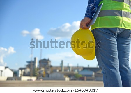 Female engineers working on a building site holding a computer and hard hat inspection warehouse. Professional Engineering ware safety and helmet work manufacturing industry project background concept