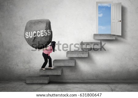 Female entrepreneur carries a boulder with Success word on her back while walking on the stairs toward a door #631800647