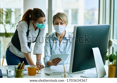 Female entrepreneurs with face masks cooperating while working on touchpad in the office.