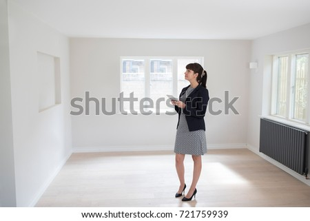 Female Estate Agent With Digital Tablet Looking Around Vacant Property For Valuation