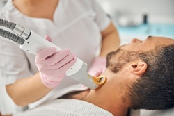 Female esthetician hands in sterile gloves removing unwanted hair from male neck with special laser device