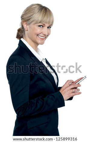 Female executive operating touch screen cellphone while smiling at camera.