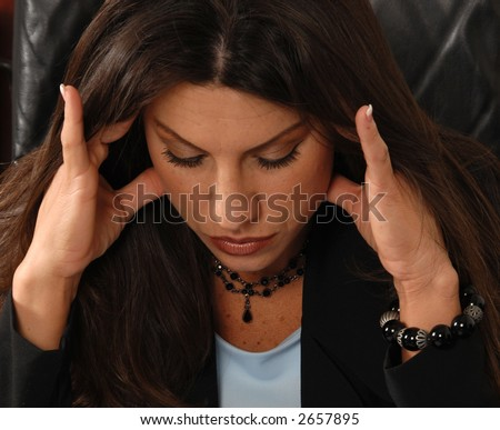 Female Executive stressed out and sitting at her desk  massaging her temples to relieve a tension headache