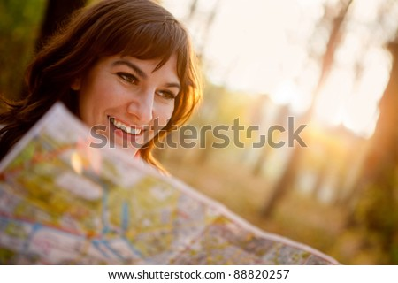 female explorer looking at a map outdoors
