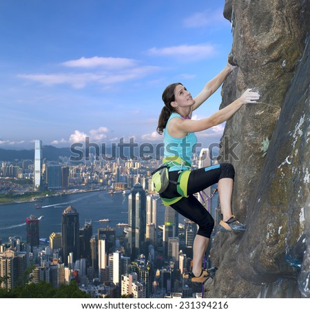 Female extreme climber conquers steep rock against modern urban landscape on the background