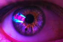 Female eye close up, with neon light. Black hole and lights in the eye. Two black dots in the eye