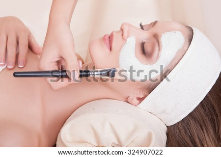 Female face closeup girl mask is applied with a brush. Beautiful girl in a beauty salon on the procedures for rejuvenation, skin lifting. Lovely woman with soft skin lying on his back in the salon spa