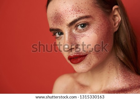 Female face covered with glossy glitter make up and empty heart-shaped picture on face. She is looking at camera while posing in studio indoors. Close up