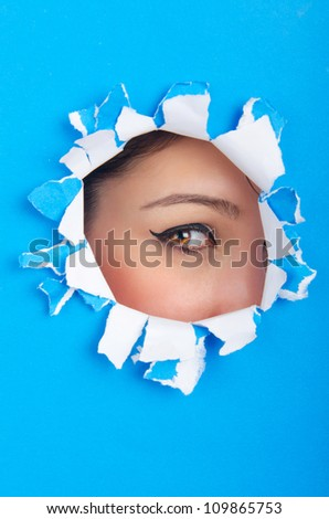Female face through the hole in paper