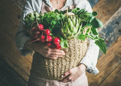 Female farmer in linen apron holding basket of fresh garden vegetables and greens in her hands, rustic wooden barn wall at background, horizontal composition. Local market or organic produce concept