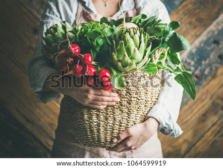 Female farmer in linen apron holding basket of fresh garden vegetables and greens in her hands, rustic wooden barn wall at background, horizontal composition. Local market or organic produce concept #1064599919