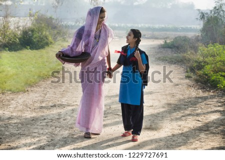 Female farmer or rural woman walking on village street along with her school going daughter carrying an iron gold pan.