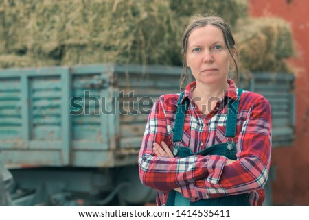 Female farmer posing in front of hay wagon. Portrait of woman farm worker in plaid shirt and bib overalls by the tractor trailer filled with dairy farm livestock feed hay bales. #1414535411