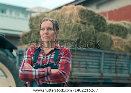 Female farmer posing in front of hay wagon. Portrait of woman farm worker in plaid shirt and bib overalls by the tractor trailer filled with dairy farm livestock feed hay bales. #1482216269