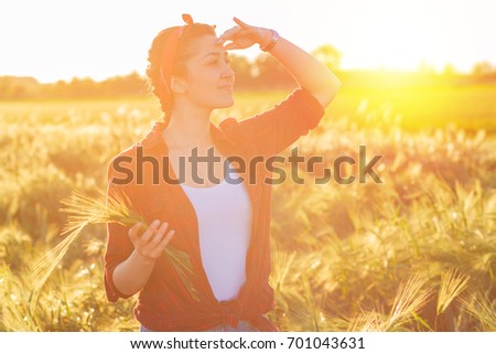 Female farmer standing in a field and examining wheat crop. - Shutterstock ID 701043631