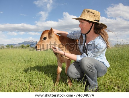 female farmer woman holding young baby calf - stock photo