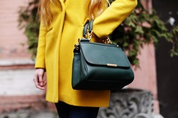 Female fashion concept. Close up. Colorful detail of yellow coat and green leather bag.  Street style