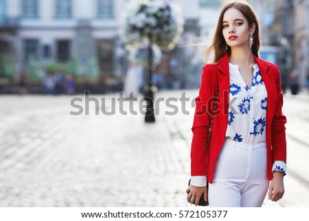 Female fashion concept. Outdoor waist up portrait of young beautiful woman posing on old street. Model wearing stylish clothes, looking at camera. Sunny day. City lifestyle. Copy, empty space for text #572105377