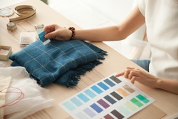 Female fashion designer holding color samples choosing fabric textile blue shades at workplace, dressmaker or tailor working at desk pointing at set palette making choice selection, close up view