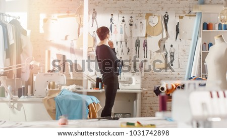 Female fashion, designer,  Looking at Drawings and Sketches that are Pinned to the Wall Behind Her Desk. Studio is Sunny. Personal Computer, Colorful Fabrics, Sewing Items are Visible.
