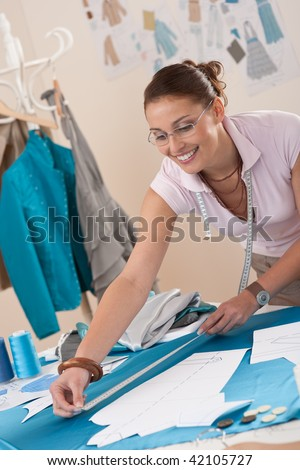 Female fashion designer working at studio with pattern cuttings and sketches