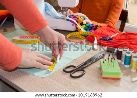 Female fashion designer working at studio with pattern cuttings and sketches. Garment industry, tailoring concept. woman seamstress sitting and sews on sewing machine #1019168962