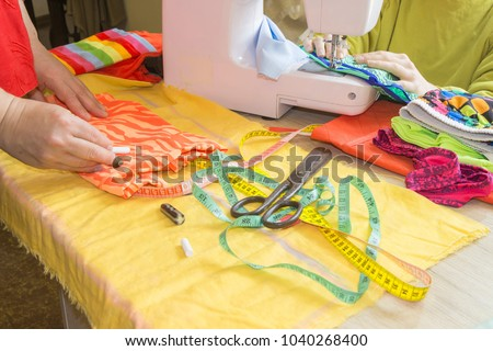 Female fashion designer working at studio with pattern cuttings and sketches. Garment industry, tailoring concept. woman seamstress sitting and sews on sewing machine #1040268400
