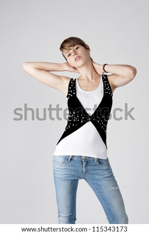 female fashion model posing at light background wearing blue jeans and black and white top - stock photo
