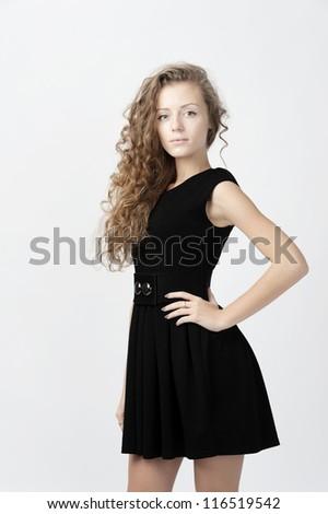 female fashion model wearing black short dress at light grey background