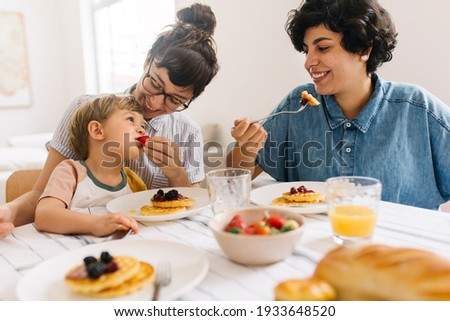 Female feeding fruits to her son while having breakfast. Lesbian couple eating breakfast with their son at home.