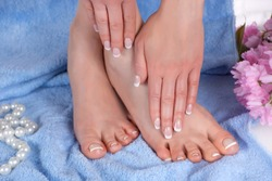 Female feet and hands with french manicure and pedicure in the spa salon on a blue towel with decorative flower and pearls. Spa and recreation concept. Close up, selective focus