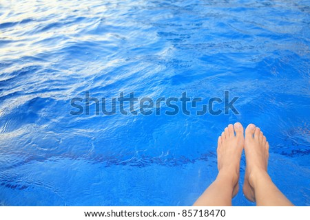 Female feet are lying over a swimming pool, while sitting on the bank of the pool