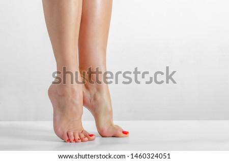 Female feet, feet stand on the fingers on a white background, Smooth skin, foot care #1460324051