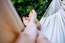 Female feet in a hammock. A woman with bare feet, with pink nail polish, relaxing and enjoying a lovely sunny summer day in a hammock. Green vegetation in background. Concept of leisure and vacation
