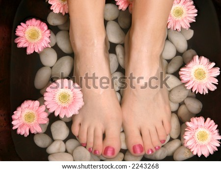 Female feet in a relaxing aromatic foot bath with massaging white stone pebble bed and floating pink flowerheads.  Feet are invigorated, skin is supple and refreshed. Pure indulgence for your feet.