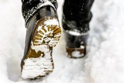 Female feet in black boots, winter walking in snow
