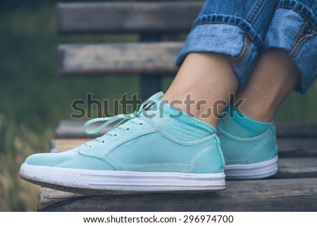 Female feet in jeans and sports shoes. Sneakers are on a wooden bench in a park close-up. Woman resting on the bench after the walk. #296974700