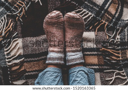 Female feet in knitted winter warm socks and in pajamas on brown checkered plaid blanket at home in cozy winter time. Top view  #1520163365