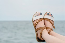 Female feet in sandals with a manicure on a sea background. Close-up