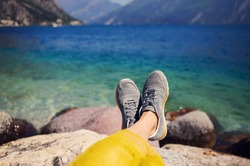Female feet in sneakers on the background of a sea and mountain  landscape sunny summer day.
