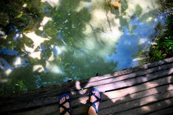 Female feet in walking sandals on wooden bridge over water spring. Summer forest hiking banner template. Woman in trekking shoes on a rustic bridge. Crossing river conceptual photo. Outdoor adventure