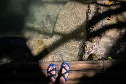 Female feet in walking sandals on wooden bridge over water spring. Summer forest hiking banner template. Woman in trekking shoes on a rustic bridge. Crossing river conceptual photo. Ecotourist trip