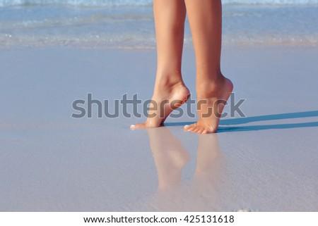 Female feet in water on the beach, white sand #425131618