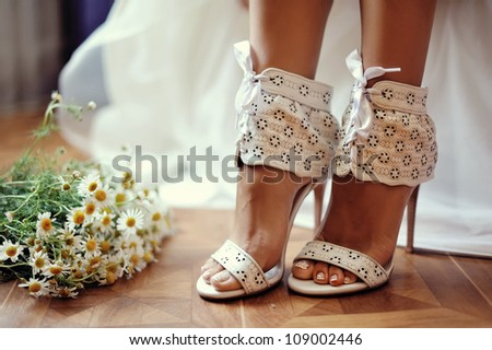 female feet in white wedding sandals with a bouquet of camomiles