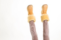 Female feet in winter yellow shoes lifted up.