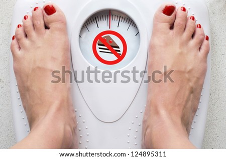 Female feet on bathroom scale with forbidden cake symbol